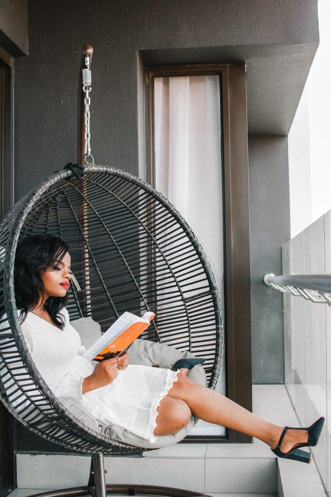 femme lisant sur son fauteuil suspendu