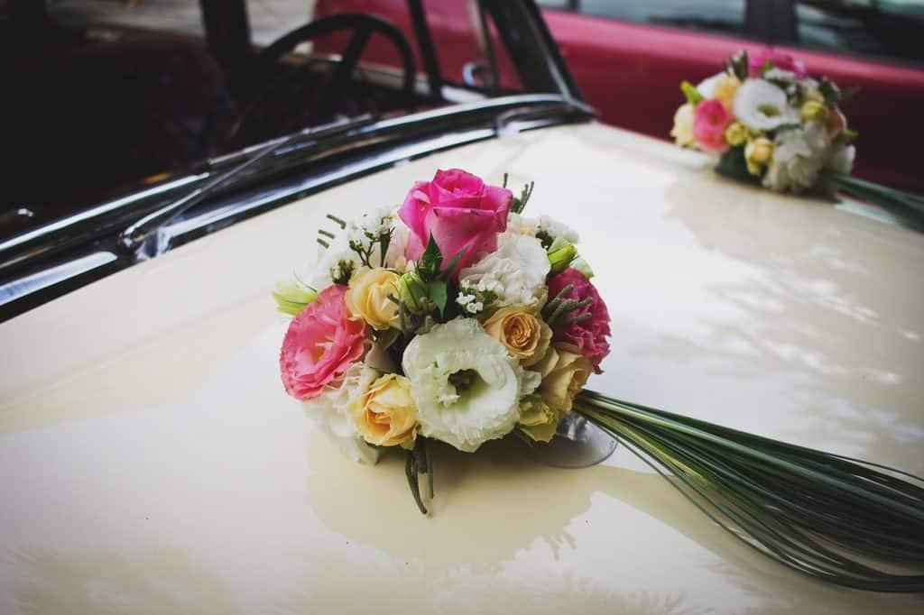 Voiture de marié avec des bouquets simple sur le capot