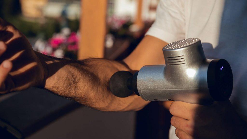 Homme utilisant pistolet de massage sur son avant bras