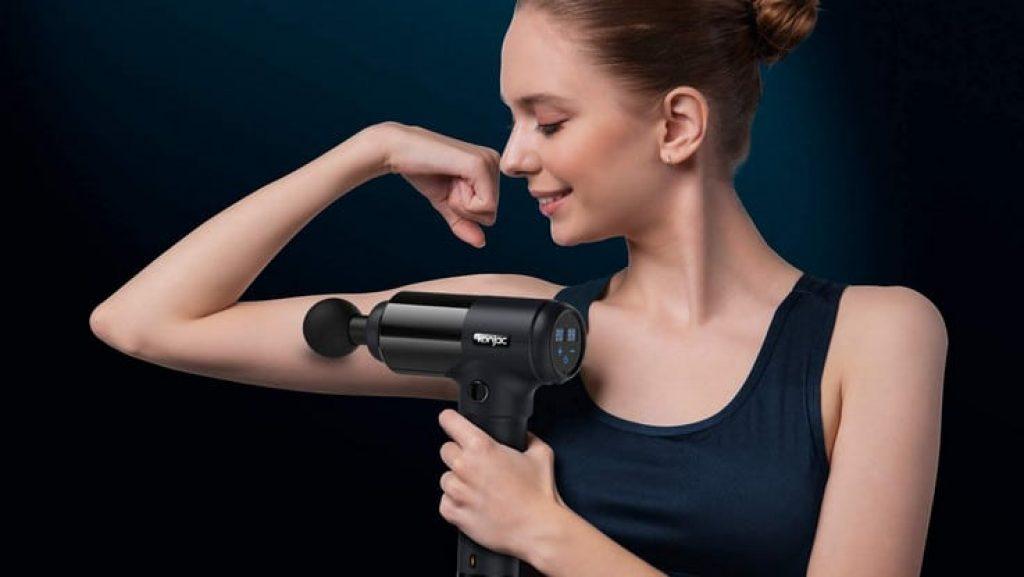 Femme utilisant un pistolet de massage sur son biceps