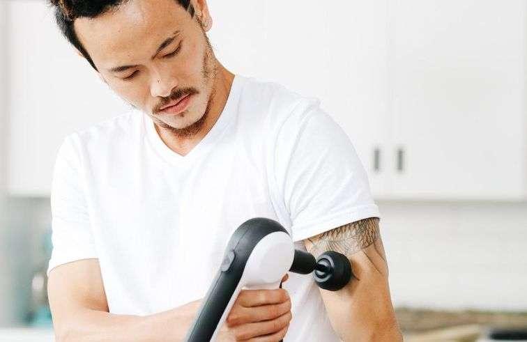Pistolet de massage utilisé par un homme sur son bras