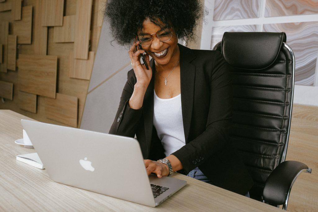 Femme assise sur une chaise de bureau ergonomique, travaillant sur son macbook