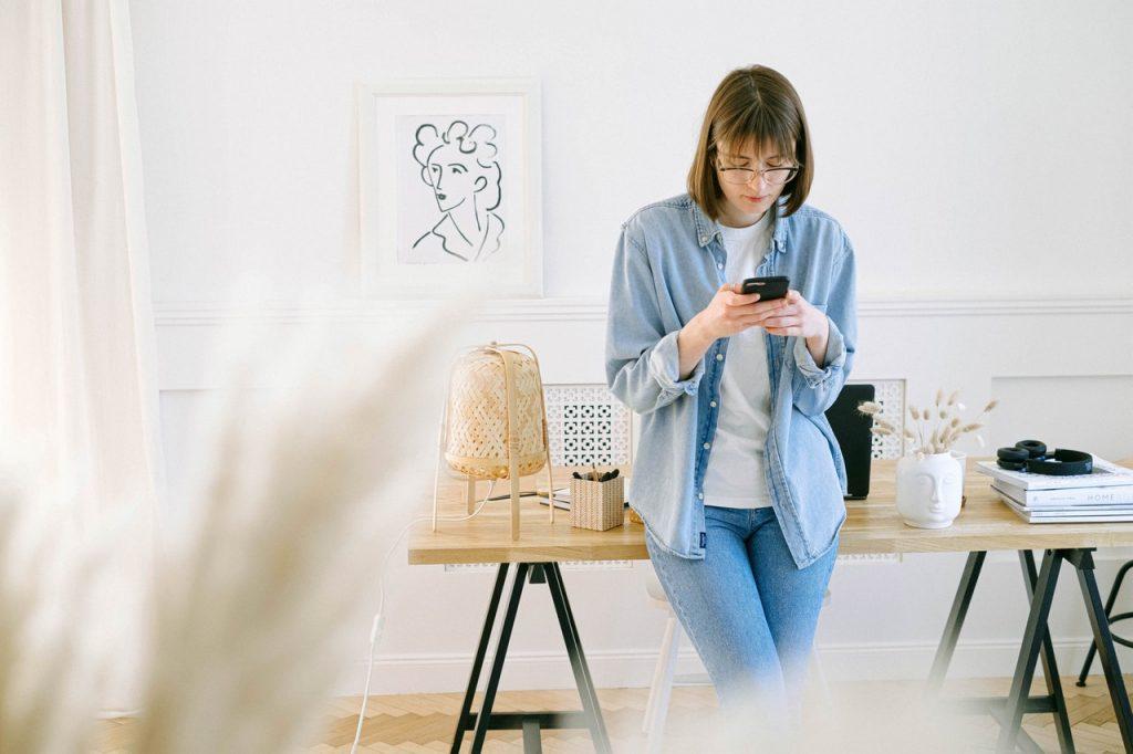 Femme debout appuyer sur son bureau répondant message