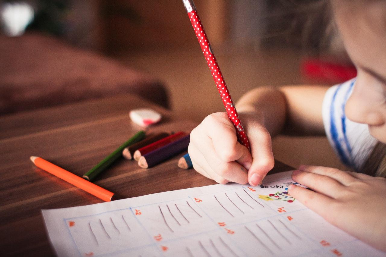 Petite fille écrivant sur un cahier à l'école avec un crayon rouge