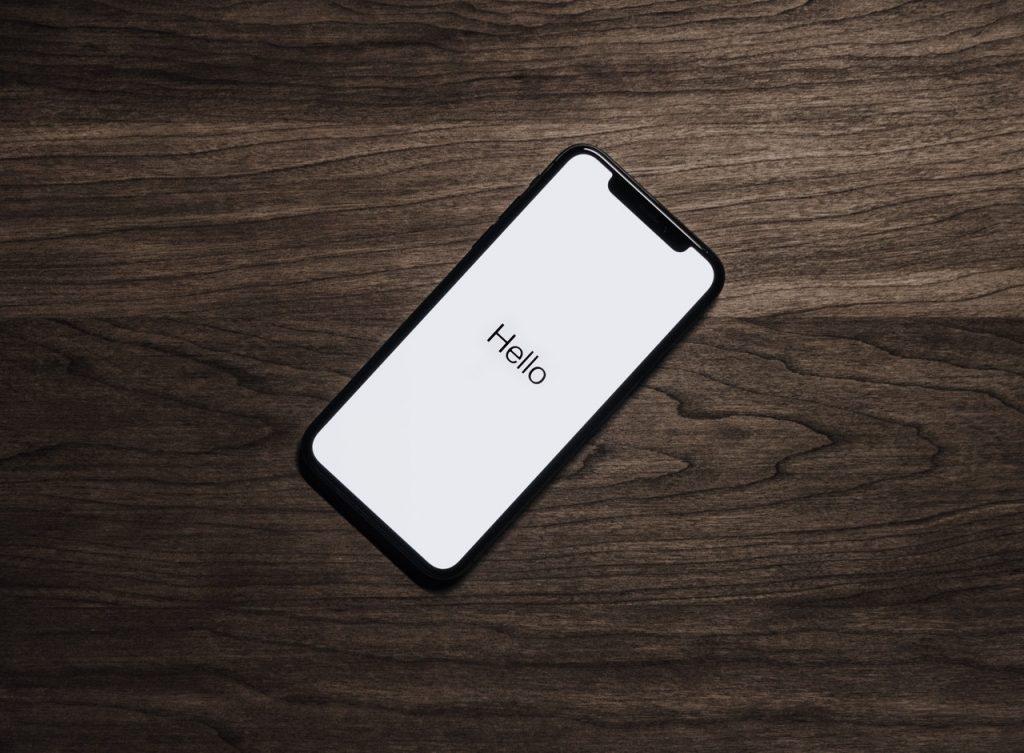 Téléphone portable noir posé sur une table en bois