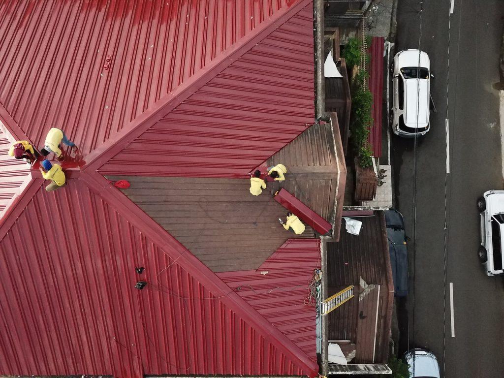 Toit rouge, avec ouvriers charpentier travaillants