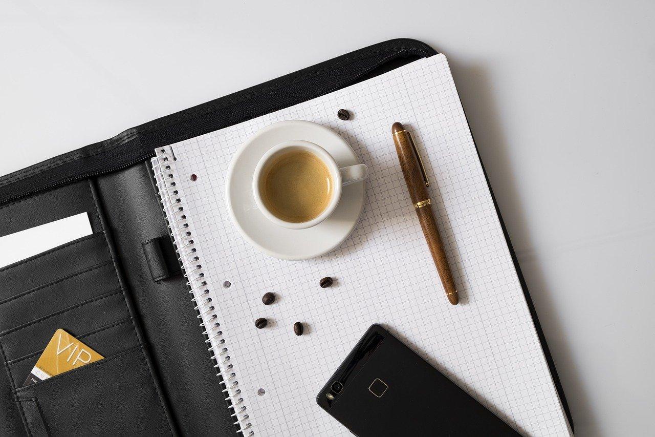Bloc, pochette de rangement, tasse à café, téléphone, carte de visite