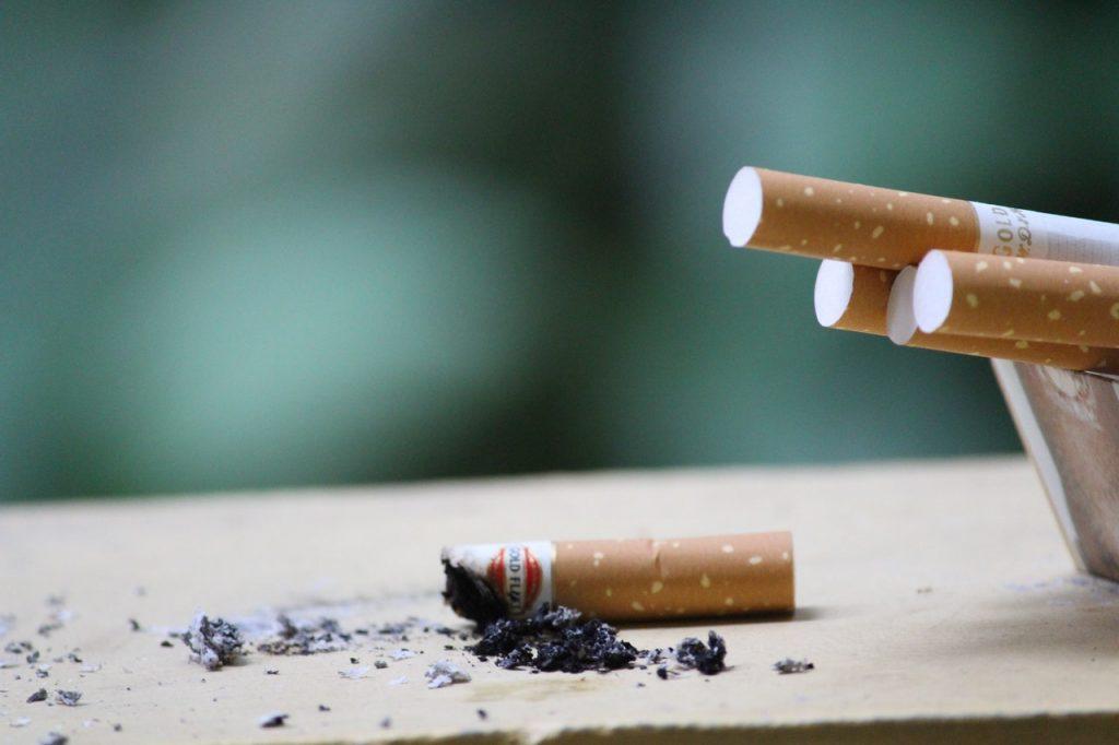 Cigarette allumée à côté d'un cendrier, cendre