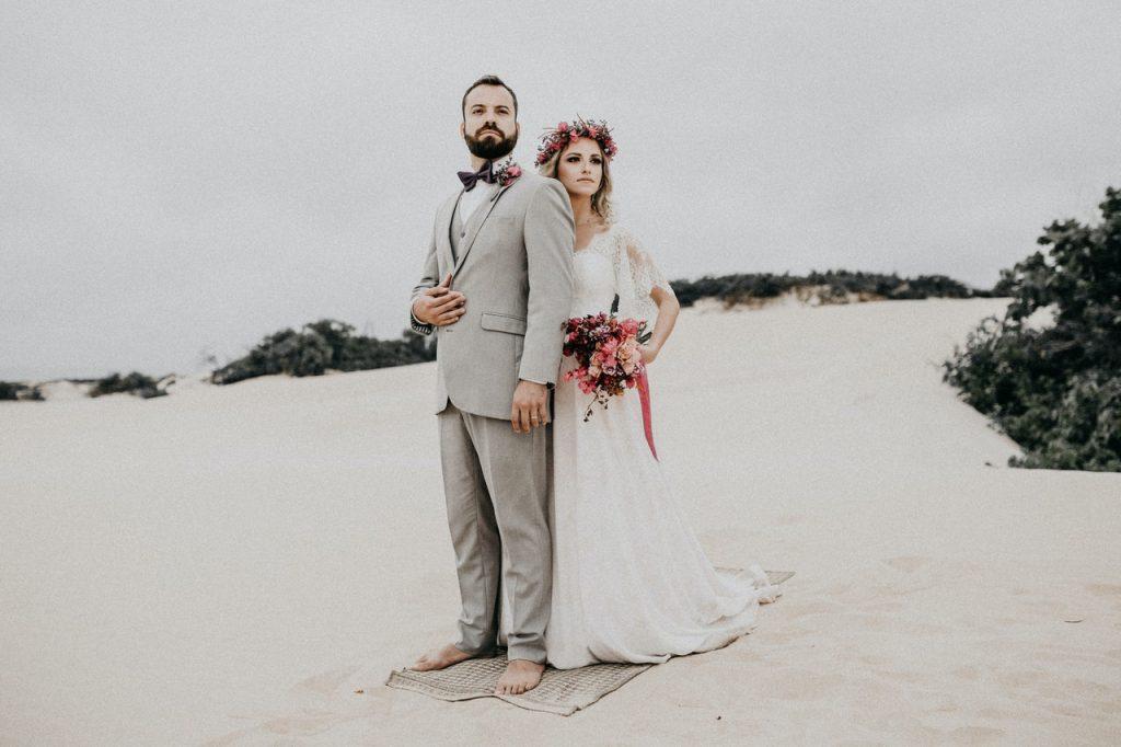 Couple de mariés sur la plage posant pour des photos
