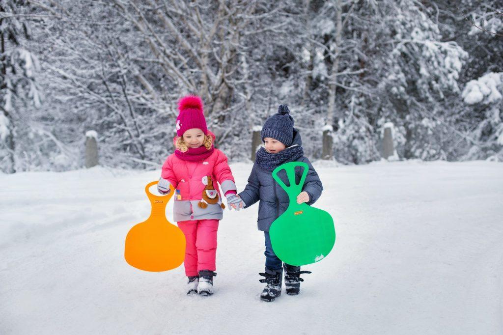 Deux enfants se tenant la main et tenant leur luge pelle pour jouer dans la neige