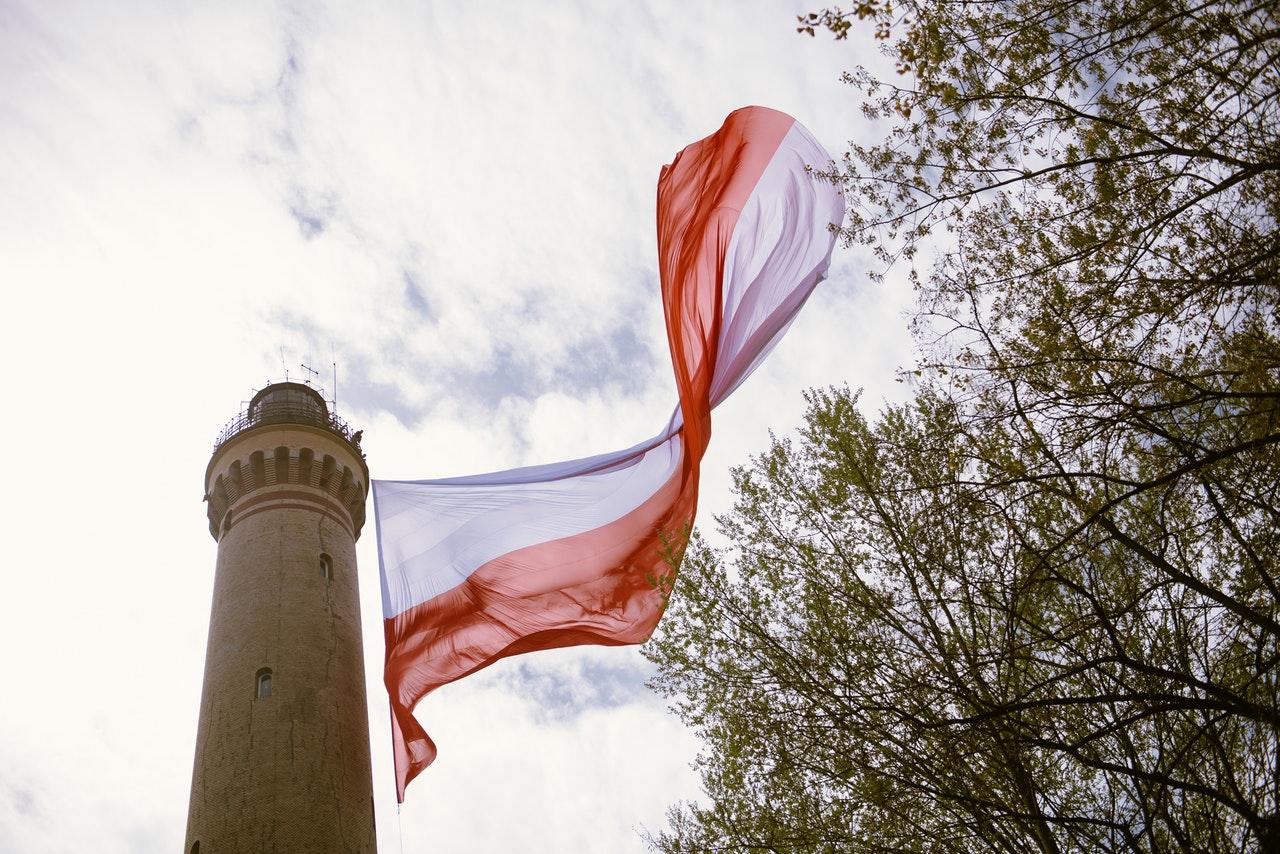 Drapeau polonais flottant devant une grande tour