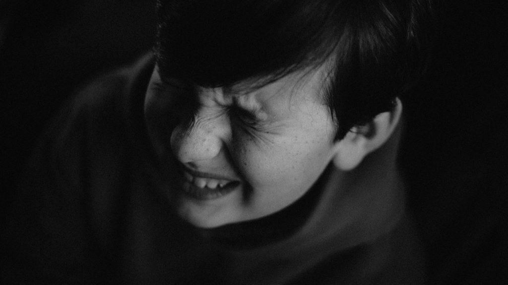 Enfant apeuré assis dans le noir