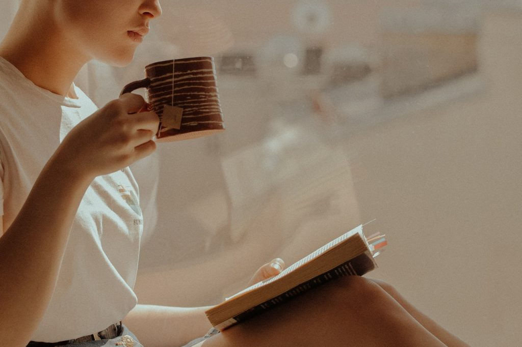 Femme tenant une tasse de thé chaude en main et lisant un livre