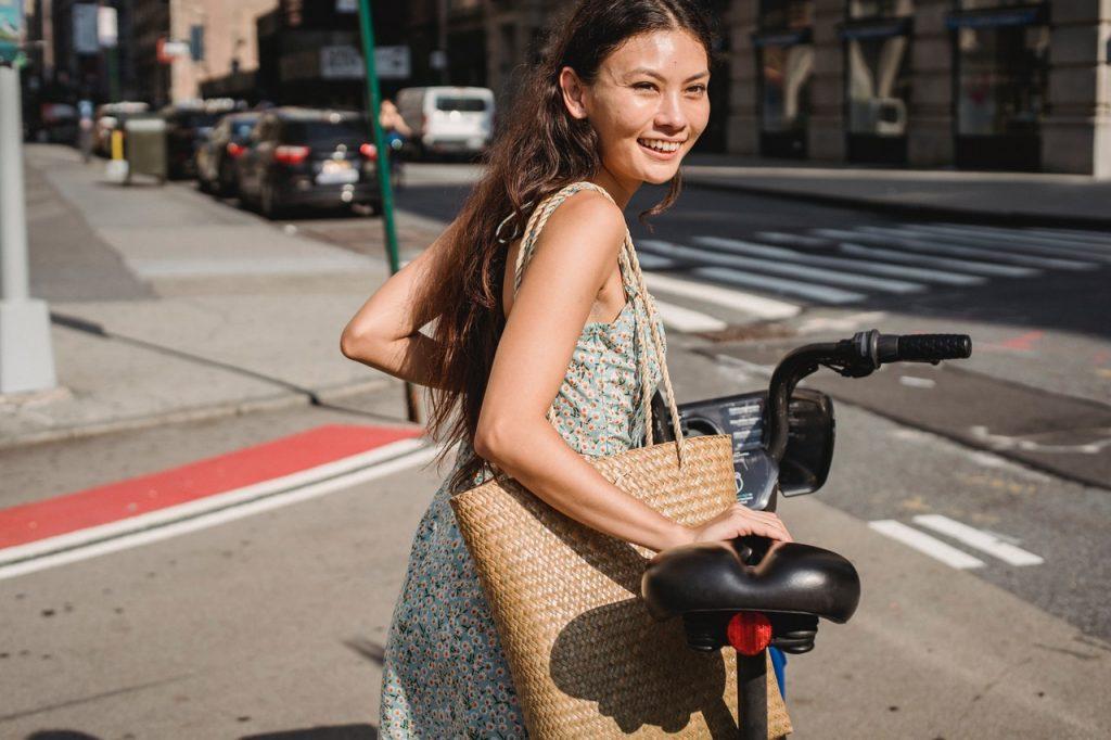 Femme professionnel tenant son vélo dans la rue