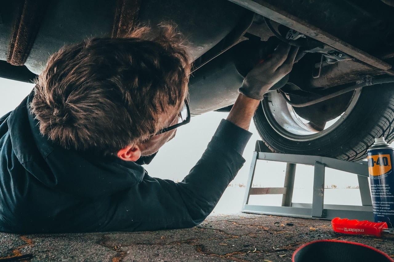 Garagiste contrôle le dessous de la voiture, mécanique
