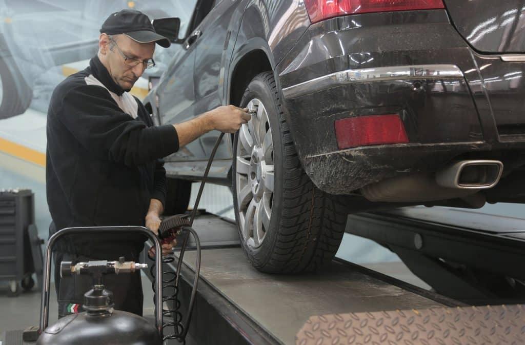 Garagiste, mécanicien, contrôlant les pneus, les gonfleants