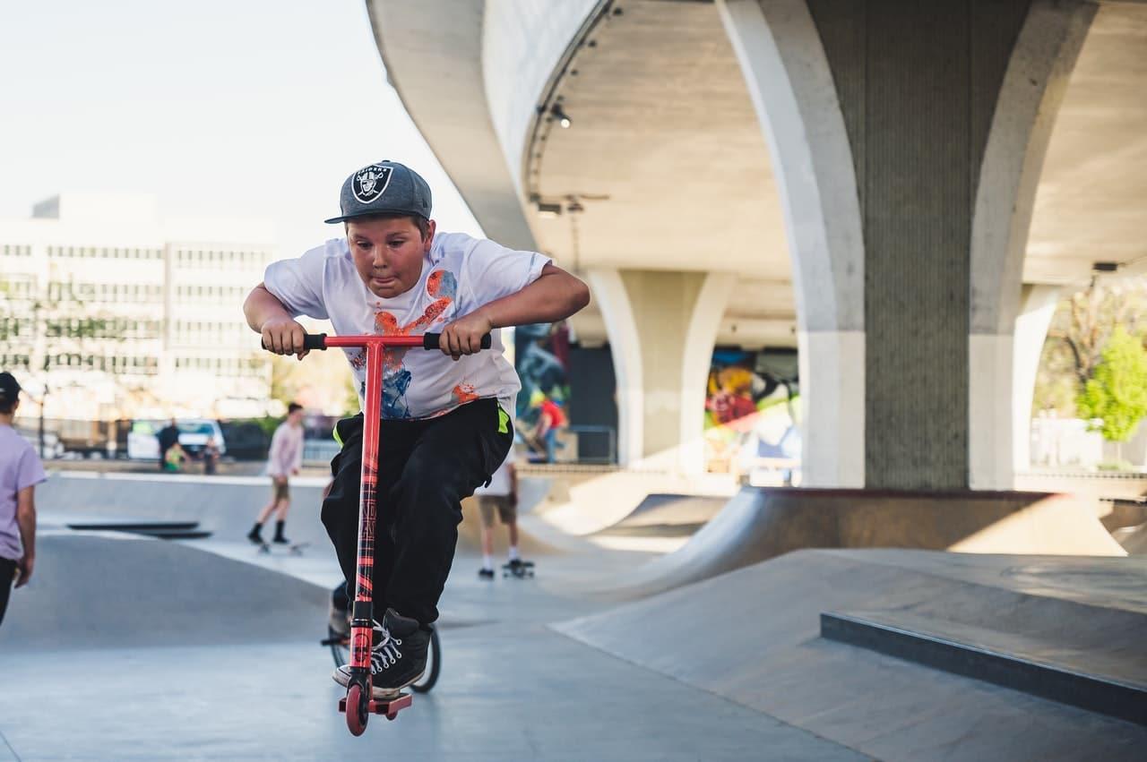 Jeune garçon faisant de la trottinette dans un skate parc
