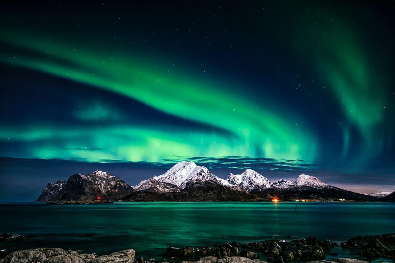Paysage norvégien, aurore boréale verte, montagne enneigée, lac
