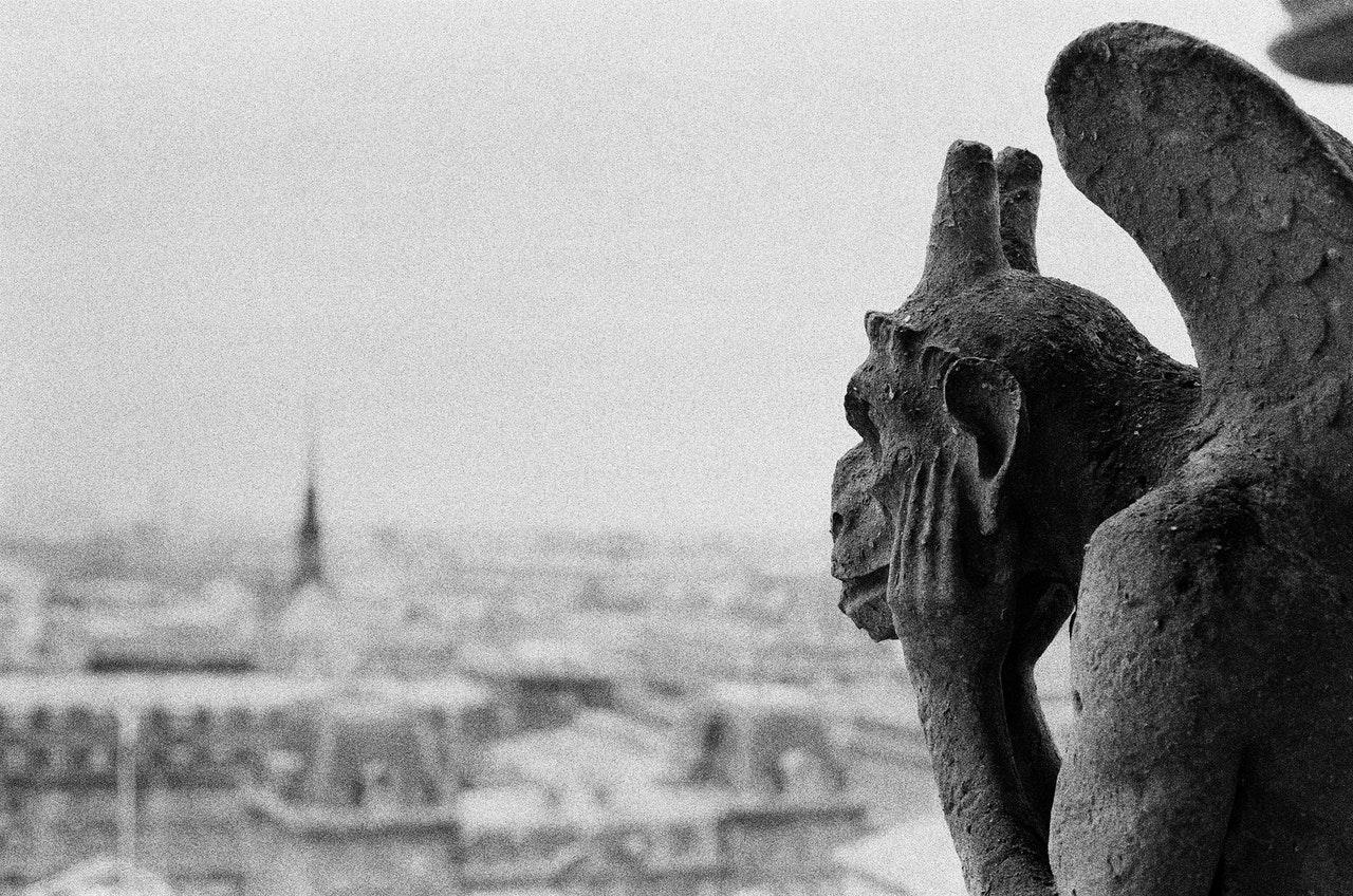 Photo en noir et blanc d'une gargouille présente sur la cathédrale de Notre Dame de Paris