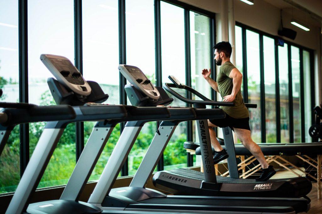 Homme courant sur un tapis, running, salle de sport, cardio et fitness, sportif