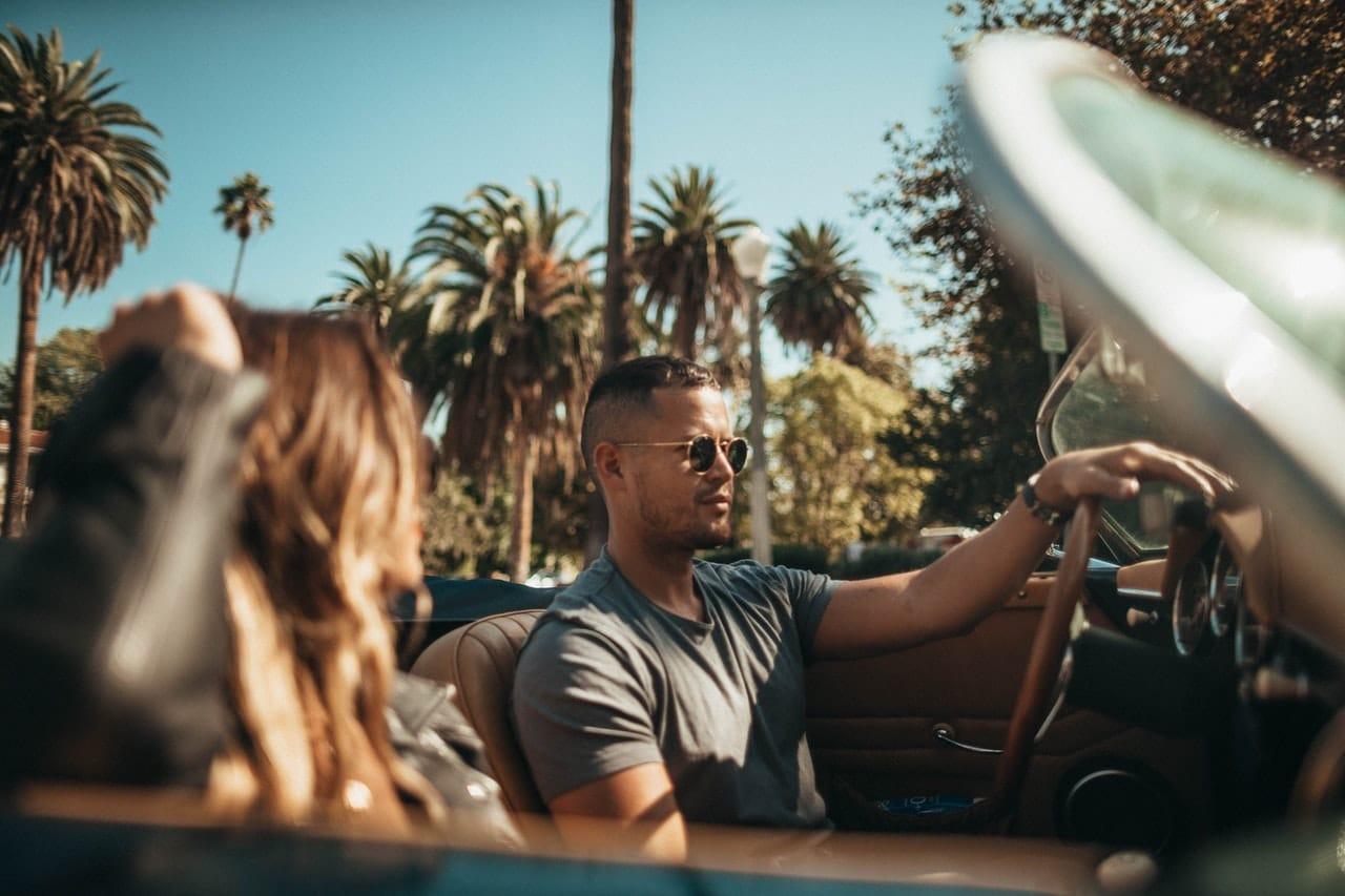 Voiture décapotable conduite par un jeune couple en Floride, palmier et soleil