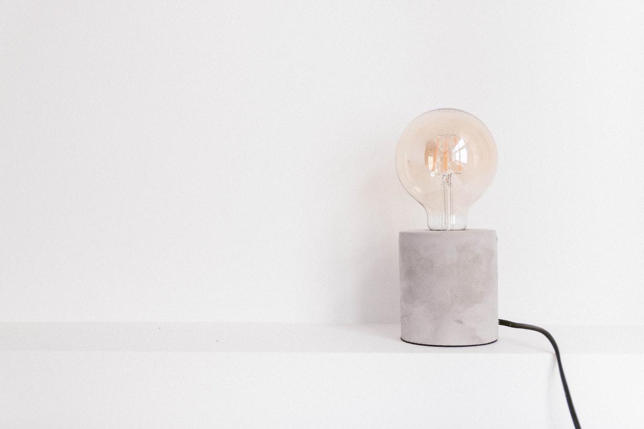 Lampe design avec une grosse ampoule, un pied en bêton