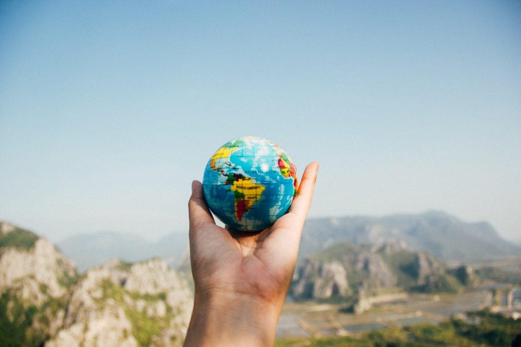 Homme tenant un petit globe terrestre entre la main