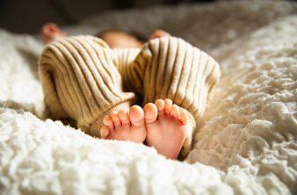 Bébé allongé sur une couverture mouton douillette, petits pieds nues