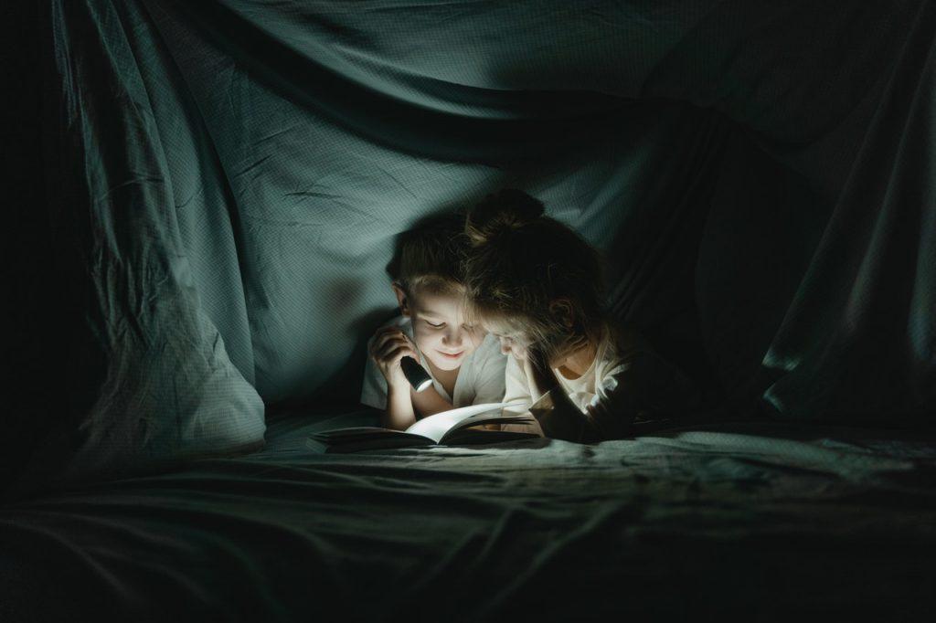Enfant lisant un livre dans une cabane de couverture avec une lampe torche