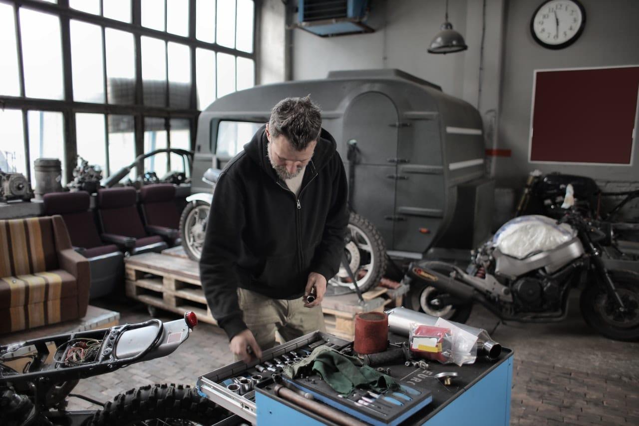 Homme bricolant dans un garage et rangeant ses outils