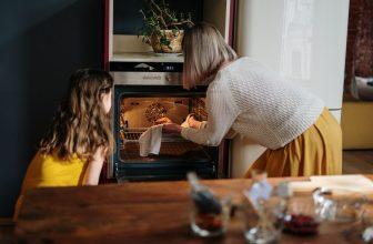 Mère et fille cuisinant dans la cuisine, utilisant un four