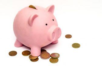 Tirelire cochon rose, avec de l'argent autour, pièces de monnaie