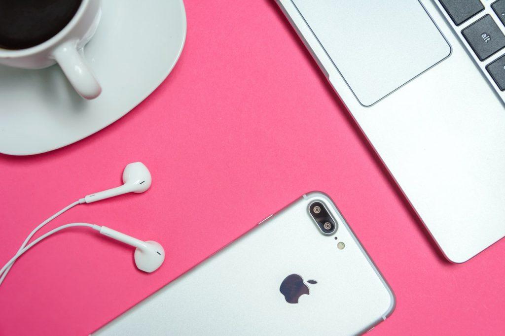 Iphone, et macbook Apple disposé sur une table rose avec une tasse de café