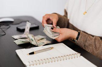 Femme comptant de l'argent et prenant des notes