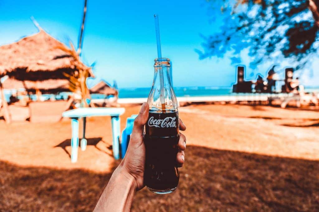 Personne à la plage tenant une bouteille de coca-cola en verre