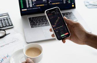 Personnes regardant des courbes d'investissements sur son mobile et sur son PC en buvant un café