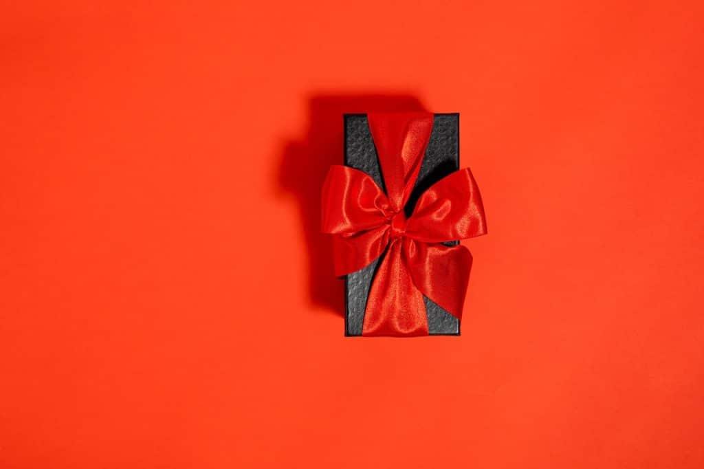 Petit cadeau noir, entouré d'un ruban large rouge faisant un nœud