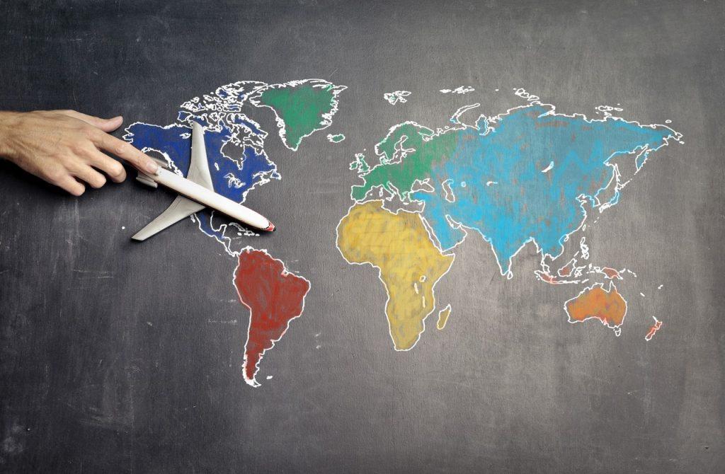 Map monde coloré avec main tenant un avion pour le voyage