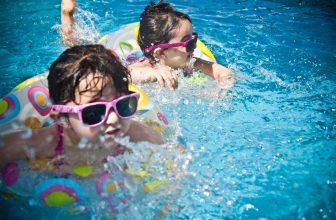 Deux enfants jouant dans la piscine avec leur bouée et portant lunette de soleil