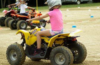Petite fille en t-shirt rose faisant du quad