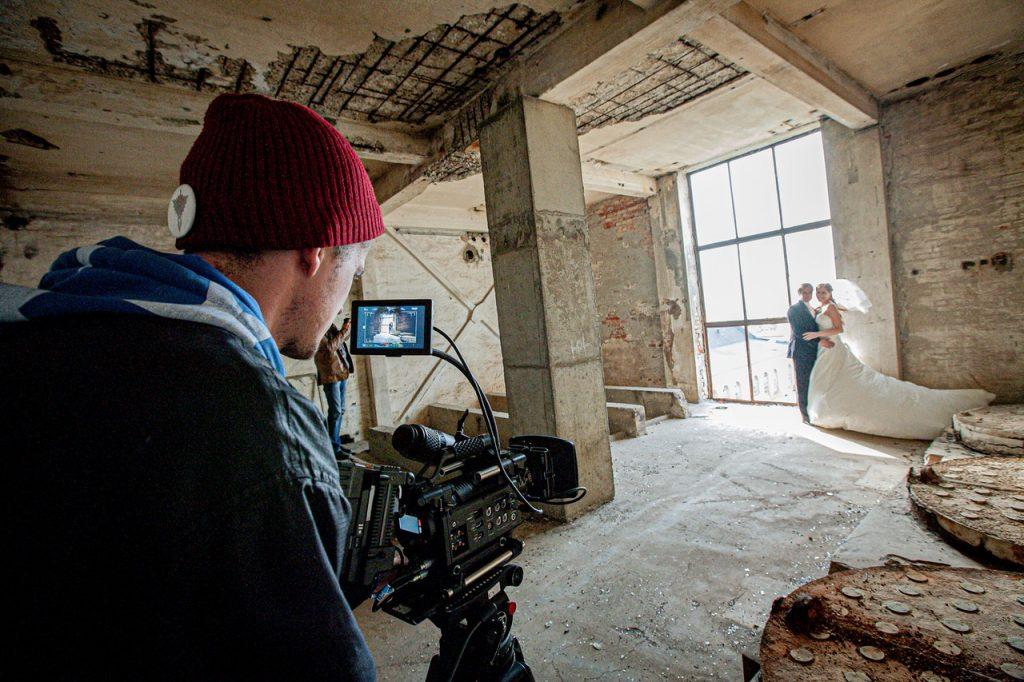 Photographe filmant des mariés dans un immeuble désafecter