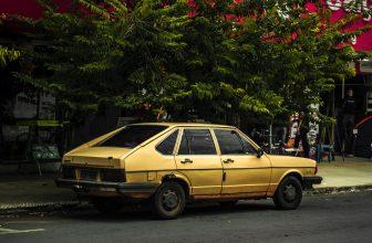 Vieille voiture jaune garée sous un arbre fleurie