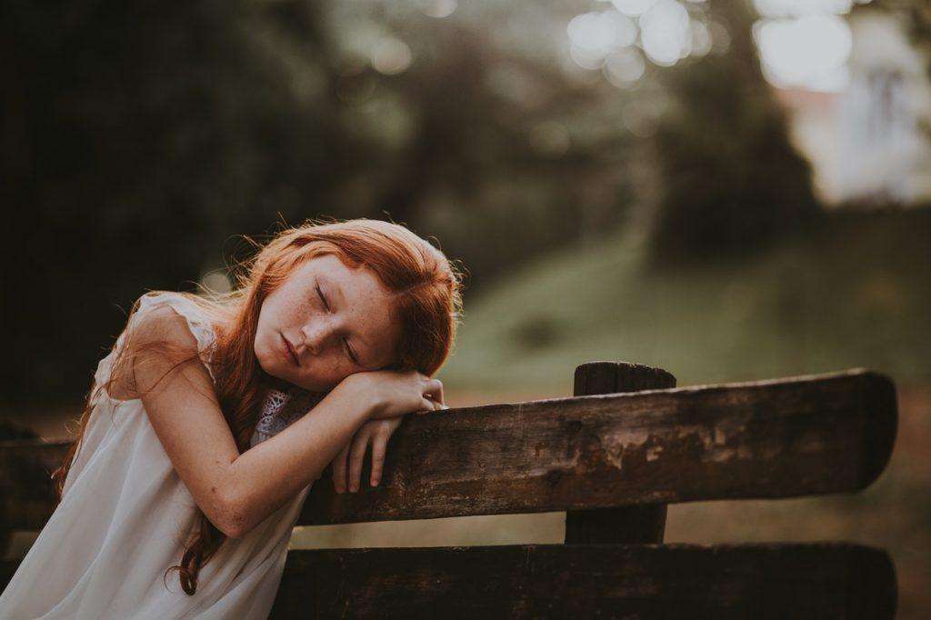 Petite fille rousse endormie sur un banc en bois