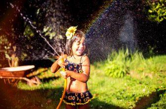 Petite fille jouant avec un tuyau d'arrosage, heureuse