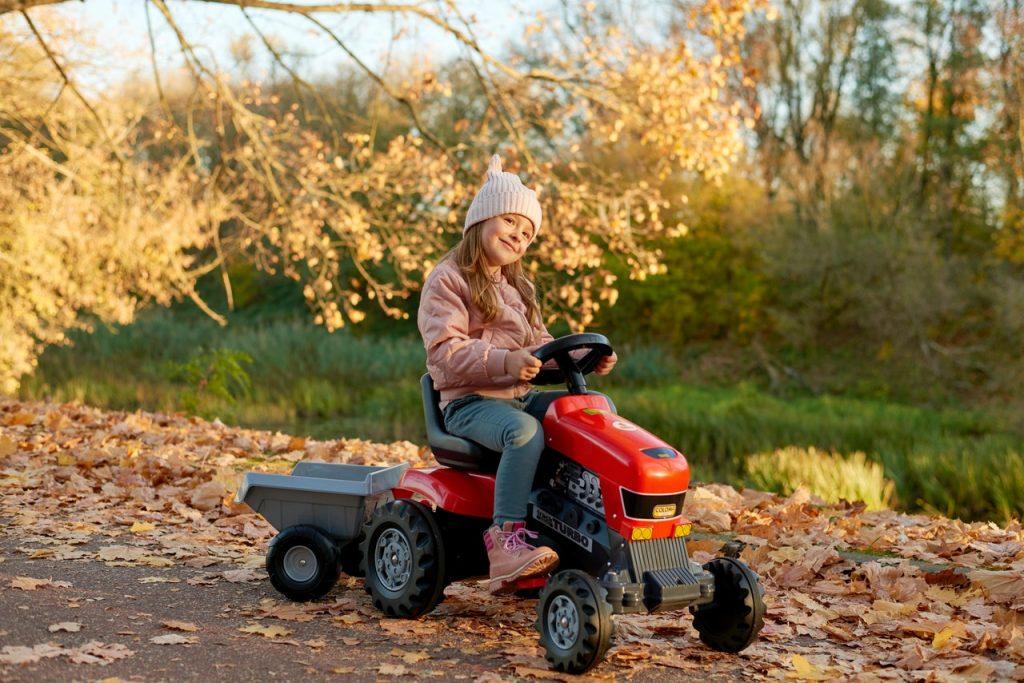 Petite fille faisant du tracteur à pédale sur un chemin en automne