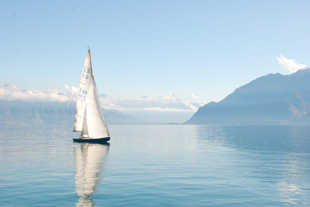 Bateau, voilier naviguant sur un lac entouré de montagnes
