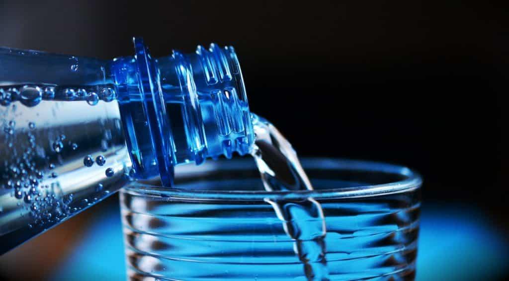 Bouteille d'eau versant dans un verre