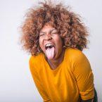 Femme métisse aux cheveux crépus tirant la langue, joyeuse et portant un haut jaune