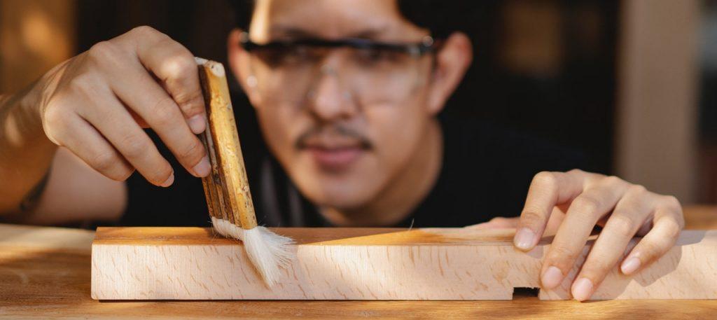 Homme peignant du bois avec un pinceau