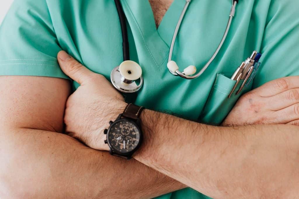 Médecin, bras croisé avec stéthoscope et stylo dans la poche